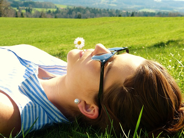 young woman lying on the grass - how to reduce cortisol - diagnost